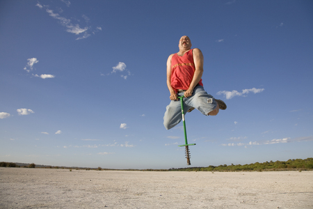Photo for A man using a pogo stick at a desolate location. - Royalty Free Image