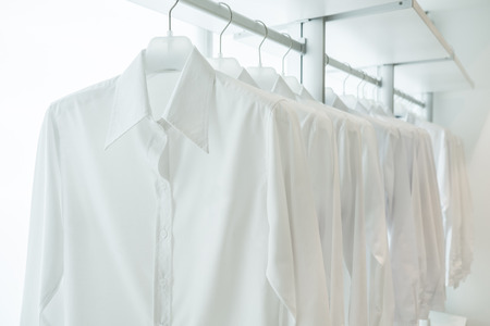 Photo pour white shirts hanging on white built-in cloths racks, with drawers and other accessories - image libre de droit