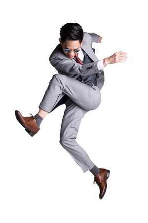 Foto per Young Asian business man in suit jumping kick pose. studio photography - Immagine Royalty Free