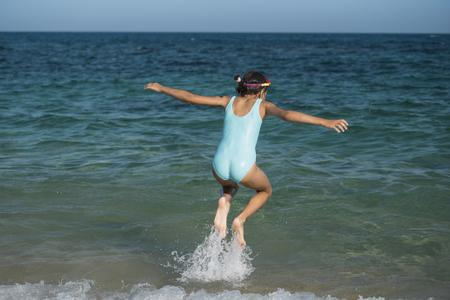 Foto de Happy child running and jumping in the waves on sea. - Imagen libre de derechos