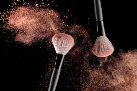 Photo pour Make-up brush with pink powder explosion on black background - image libre de droit