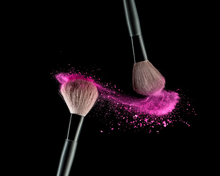 Foto de Make-up brush with pink powder explosion on black background - Imagen libre de derechos