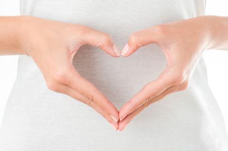 Photo pour The form of heart shaped by female hands on body background isolated on white. - image libre de droit