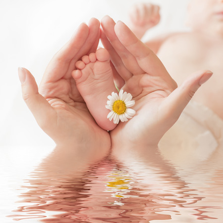 Foto de Baby foot with camomile in mommy's hands on water surface, shallow DOF. - Imagen libre de derechos