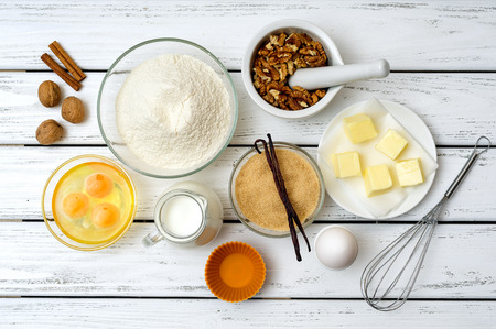 Photo pour Baking cake in rural kitchen -  recipe ingredients (eggs, flour, milk, butter, sugar, walnuts, spices) on white wooden table from above. - image libre de droit