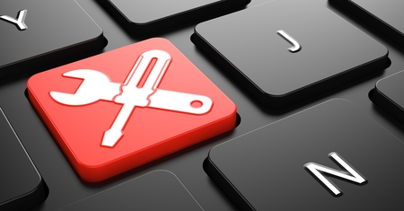 Foto de Crossed Screwdriver and Wrench on Red Button on Black Computer Keyboard. - Imagen libre de derechos