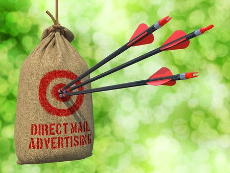 Foto de Direct Mail Advertising - Three Arrows Hit in Red Target on a Hanging Sack on Natural Bokeh Background. - Imagen libre de derechos