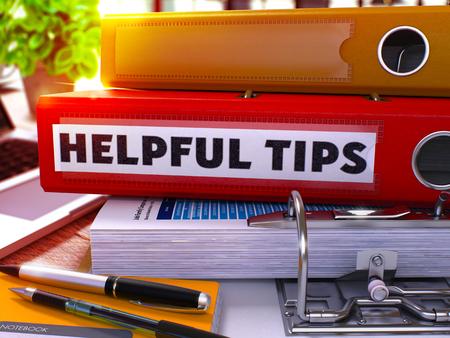 Foto de Red Office Folder with Inscription Helpful Tips on Office Desktop with Office Supplies and Modern Laptop. Helpful Tips Business Concept on Blurred Background. Helpful Tips - Toned Image. 3D Render. - Imagen libre de derechos