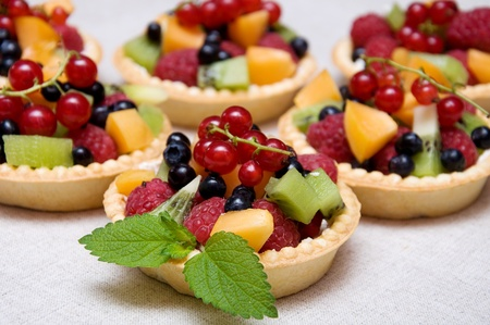 Sweet fruit dessert with raspberries, apricot, kiwi and blueberries in tartl