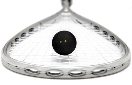 Close up of a squash racket and ball over white