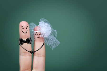Foto per Two happy fingers decorated as bride and groom with veil and bow tie - Immagine Royalty Free