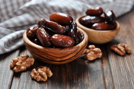 Photo for Dates fruit in a wooden bowl closeup on wooden background - Royalty Free Image