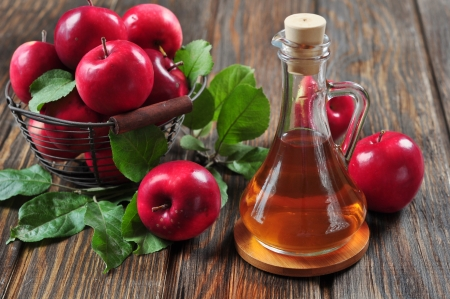 Photo for Apple cider vinegar in glass bottle and basket with fresh apples - Royalty Free Image
