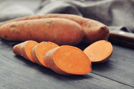 Photo for Raw sweet potatoes on wooden background closeup - Royalty Free Image