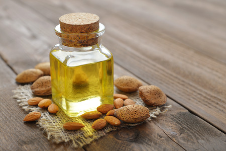 Photo for Almond oil in bottle on wooden background - Royalty Free Image