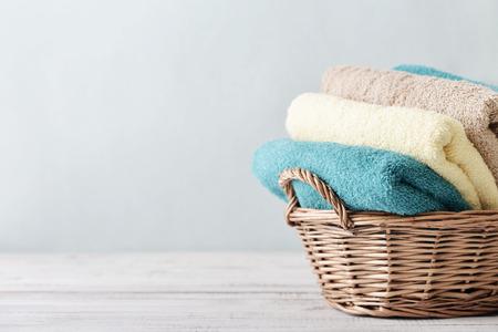 Foto de Bath towels of different colors in wicker basket on light background - Imagen libre de derechos