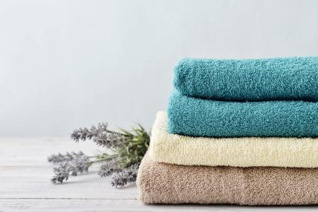 Foto de Stack of bath towels with lavender flowers on light wooden background closeup - Imagen libre de derechos