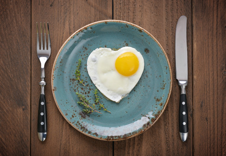 Photo for Fried egg in shape of heart on blue plate top view - Royalty Free Image