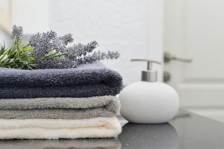 Foto de Soap dispenser with a stack of towels in a bathroom closeup - Imagen libre de derechos