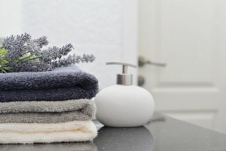 Foto de Stack of towels with a soap dispenser  in a bathroom closeup - Imagen libre de derechos
