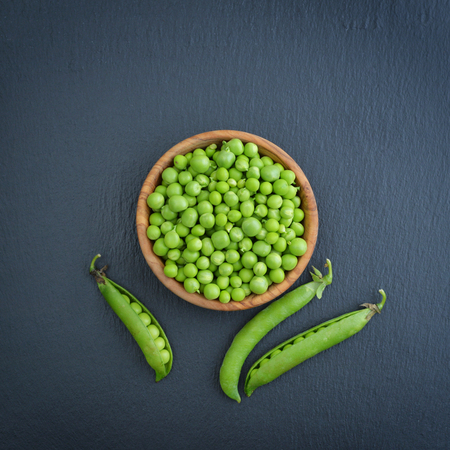 Foto de Green peas in wooden bowl on black slate background, top view - Imagen libre de derechos