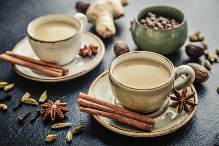 Photo for Traditional indian drink - masala chai tea (milk tea) with spices on black slate  background - Royalty Free Image