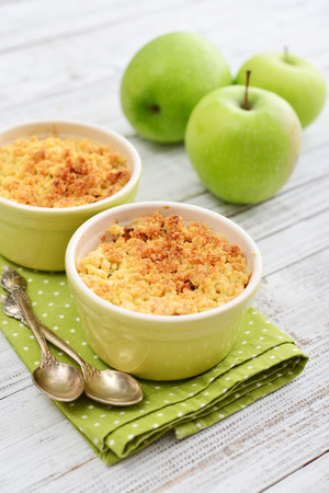 Photo for Apple crumble in small baking dish with fresh apples on wooden background - Royalty Free Image