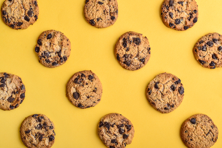 Foto de Cookies pattern on the yellow background. Top view of chocolate chip cookies - Imagen libre de derechos
