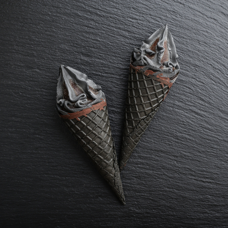 Photo for Black ice cream in cone on black slate background, top view - Royalty Free Image