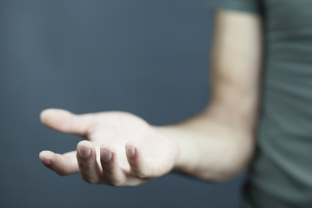 Foto de male is standing and shows outstretched hand with open palm - Imagen libre de derechos