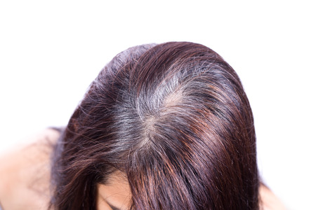 Foto de Young woman shows her gray hair roots - Imagen libre de derechos