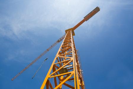 Foto de construction cranes and the blue sky with clouds. Taken from the bottom up - Imagen libre de derechos