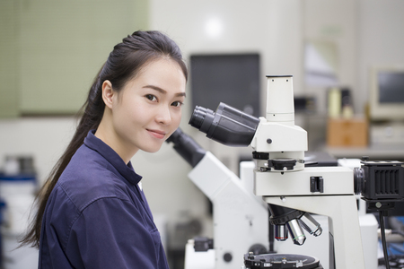 Foto de female scientist looking in microscope in laboratory Laboratory Microscope - Imagen libre de derechos