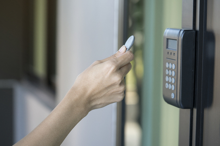 Photo for young woman using RFID tag key to open the door - Royalty Free Image