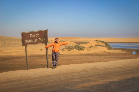 Photo for Young girl tourist backpacker in the Dorob National Park part of Dead Vlei in the southern part of the Namib Desert, in the Namib-Naukluft National Park in Namibia. Sossusvlei - Royalty Free Image