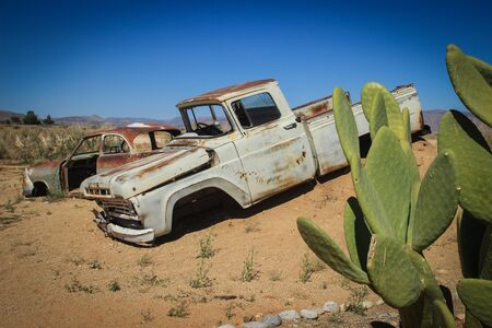 Photo for Abandoned old rusty cars in the desert of Namibia surrounded by cactus near the Namib-Naukluft National Park. Africa - Royalty Free Image