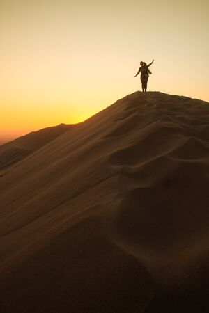 Photo for The highest sand dunes in the world at sunset in Namib Desert, in the Namib-Nacluft National Park in Namibia. Sossusvlei. Young woman tourist with backpack stands on top - Royalty Free Image