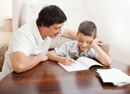 Photo for Father helping son do homework. Parent helps his child - Royalty Free Image