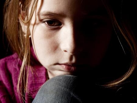 Sad child on black background. Portrait depression girl