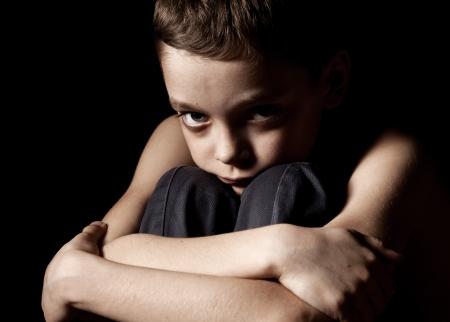 Sad boy on black background. Portrait depression boy