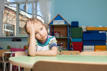 Photo pour Sad child in kindergarten. Depression girl in nursery school - image libre de droit