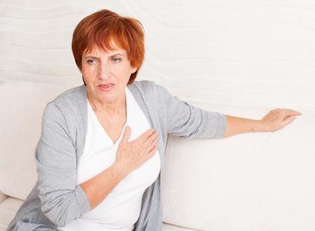 Foto de Cardiac pain. Mature woman holds her heart - Imagen libre de derechos