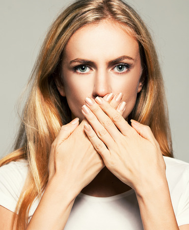 Woman with closed mouth. Female covers her mouth with her hands. Silence, fear, violence.