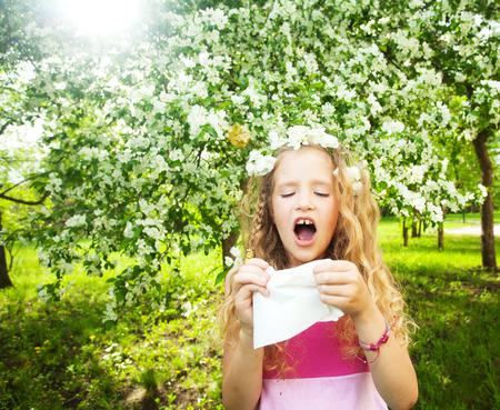 Foto de Sneezing girl. Child with a handkerchief. Allergy - Imagen libre de derechos