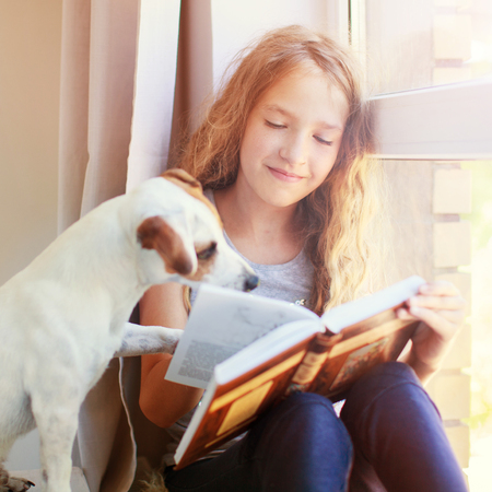 Foto de Child with dog reading book at home. Girl with pet sitting at window at read - Imagen libre de derechos