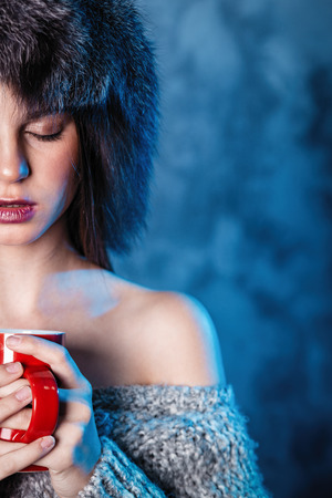 Photo for Merry Christmas and happy new year! Adorable female hold red cup. Close portrait on gray background. Girl in fur hat and sweater dreaming looks cheeky - Royalty Free Image