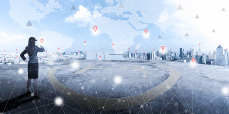 Foto de Businesswoman standing on top of business building and looking forward to city with network connection on map in the sky and sunlight. International business, world wide connecting technology concept. - Imagen libre de derechos