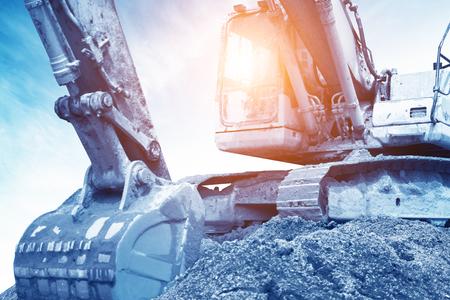 Foto de heavy orange excavator with shovel standing on hill with rocks - Imagen libre de derechos