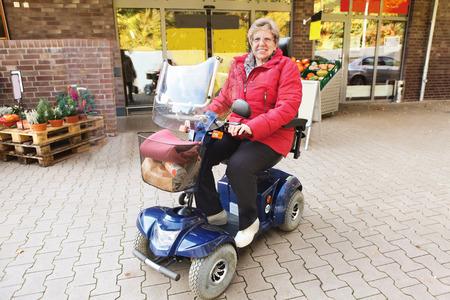 Foto de Senior woman driving with her scooter to the supermarket - Imagen libre de derechos