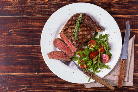 Photo for Ribeye steak with arugula and tomatoes on  dark wooden background. - Royalty Free Image